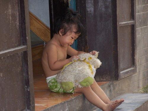 可爱的小娃娃抱着绒娃娃